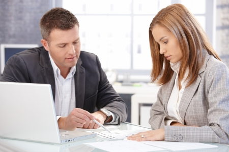 reunion de trabajo: Empresarios trabajando juntos en la Oficina brillante, sentado en el escritorio.