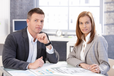 co work: Attractive young businesspeople working together, sitting at desk in bright office, smiling.