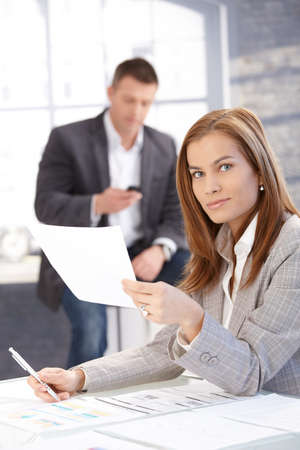 Attractive young female working at desk in bright office, man texting in background. photo
