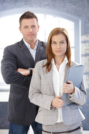 Young businesspeople standing in office, smiling. photo