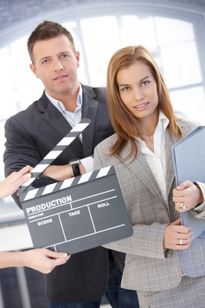 making face: Attractive businesspeople with clapper board, during shooting a film, smiling.