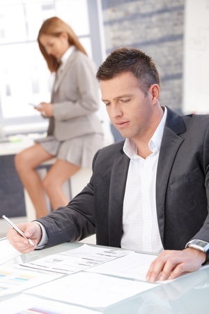 Businessman working in office sitting at desk, woman texting in background photo