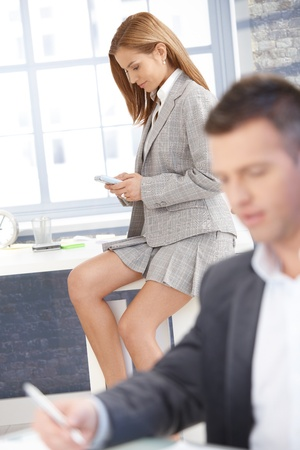 concentrating: Sexy businesswoman in mini skirt texting in office, businessman working at desk.