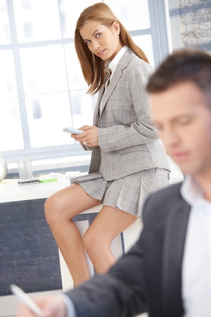 skirt suit: Pretty businesswoman sitting on desk in bright office, texting, businessman working in background. Stock Photo