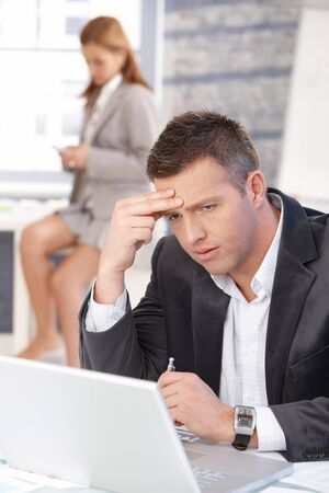 Businessman working on laptop in bright office, woman texting in background.
