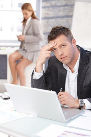 Middle-aged businessman sitting troubled at desk, working on laptop, woman texting in background. photo