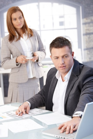 Handsome businessman working at desk, using laptop, assistant bringing coffee. photo
