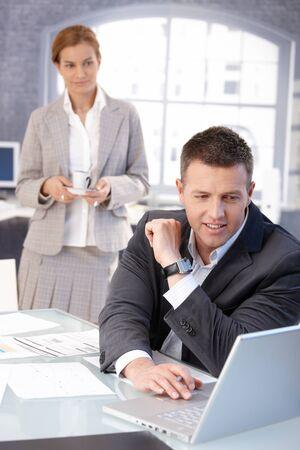 ambos: El hombre de negocios trabajando en escritorio en la Oficina brillante, obtenci�n de caf� de bastante ayudante, ambos sonriendo.