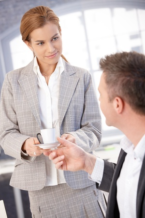 Attractive young secretary handing coffee cup to boss in bright office, smiling. photo