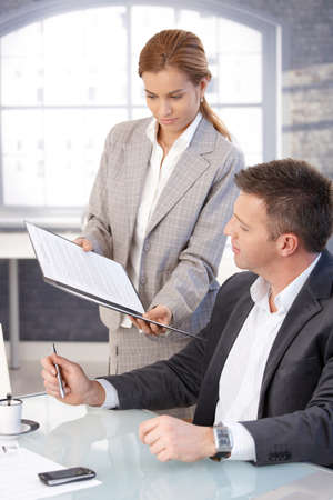 bringing: Manager sitting at desk, secretary bringing contract to sign. Stock Photo