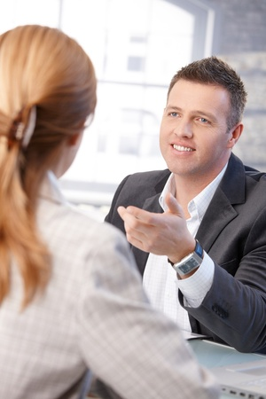candidate: Cheerful male manager interviewing female candidate in office.