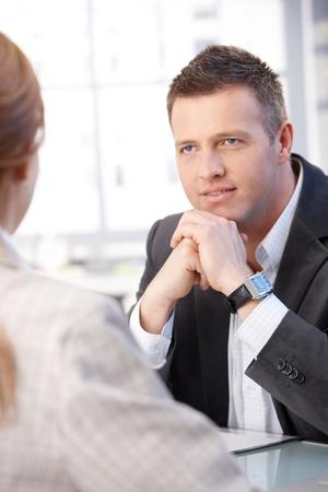 prestar atencion: Gente de negocios hablando en hombre de negocios de escritorio mirando al compañero de trabajo.