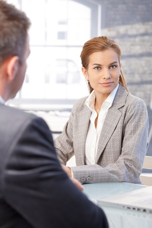 interviewed: Attractive young woman sitting at desk in bright office, being interviewed.