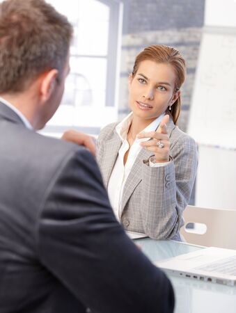 candidate: Attractive female hr manager interviewing male applicant in bright office. Stock Photo