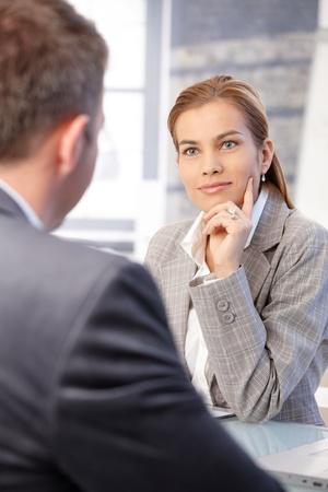 prestar atencion: Hermosa empresaria entrevistar a candidatos masculinos en Oficina brillante, sonriendo.