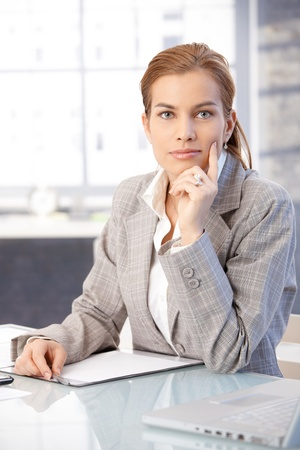 Beautiful businesswoman sitting at desk in office, thinking. photo