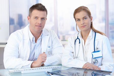 Young doctors sitting at desk in office, consulting. Stock Photo - 8747084
