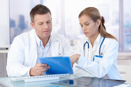 medical physician: Young doctors discussing diagnosis in bright office.