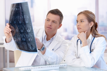 Two doctors studying x-ray image, consulting in bright office.