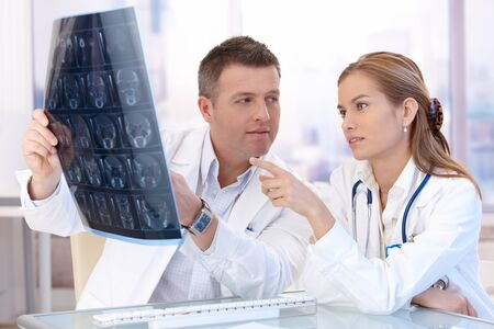Male and female doctors consulting in bright office, discussing x-ray image. photo