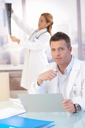 uniformes de oficina: Masculino m�dico sentado en el escritorio, hacer el papeleo, doctora en segundo plano mirando la imagen de rayos x. Foto de archivo