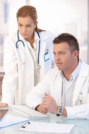 consultant physicians: Young attractive doctors working together in bright office. Stock Photo