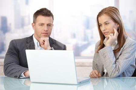 reunion de trabajo: J�venes empresarios mediante el ordenador port�til, trabajando juntos en la sala de reuniones.