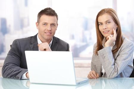 reuniones empresariales: Empresarios felices sentado en la sala, trabajando en equipo port�til, de reuniones sonriendo. Foto de archivo