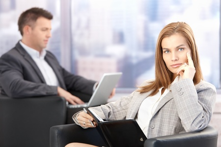 Attractive businesswoman sitting in office lobby in conference break, looking at organizer. photo