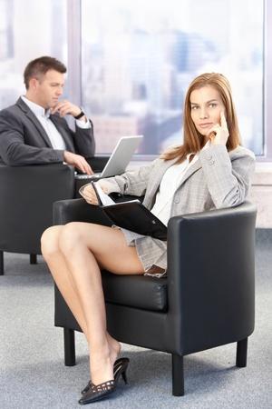 Sexy businesswoman sitting in office lobby during conference break, looking at organizer. photo