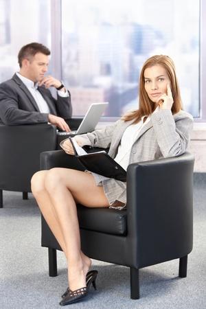 donne mature sexy: Sexy imprenditrice seduto in ufficio Hall durante la pausa della conferenza, guardando Organizzatore. Archivio Fotografico