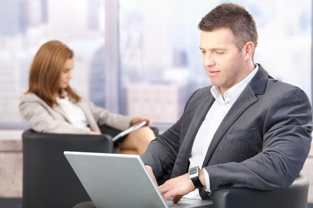 Businesspeople sitting in hallway during conference break. Stock Photo - 8747145