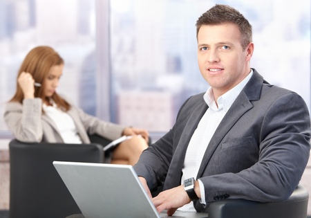 Middle-aged businessman using laptop, sitting in office lobby, having conference break, smiling. photo