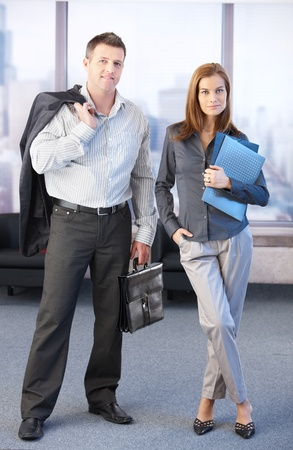 Young businesspeople standing in office lobby, smiling. Stock Photo - 8747148