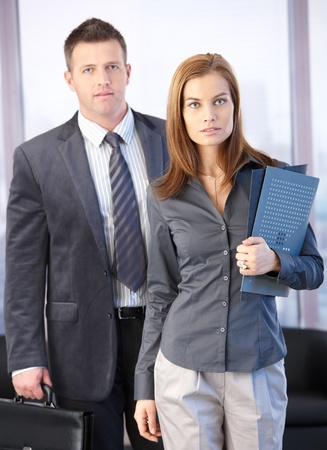 Boss and secretary going to business meeting, holding files and briefcase. photo