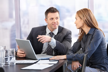 Young attractive businesspeople negotiating in bright boardroom, smiling.