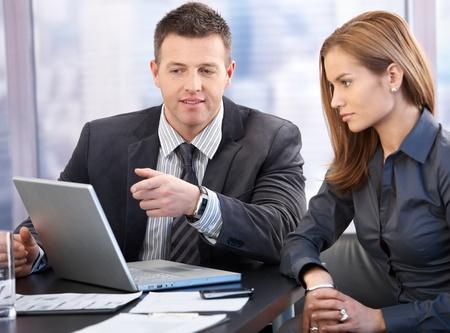 two people talking: Atractivos empresarios j�venes con la discusi�n en la sala de juntas. Foto de archivo