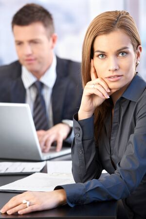 Portrait of attractive businesswoman at table, man in background working on laptop. photo