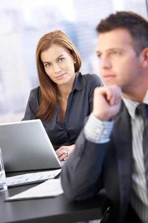 Portrait of beautiful businesswoman smiling in meeting room, man in background. Stock Photo