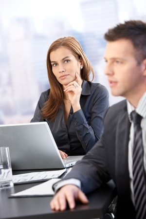 Portrait of young businesswoman sitting at table, using laptop, man in background. Stock Photo