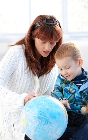 Mother and cute little kid studying globe together at home. photo