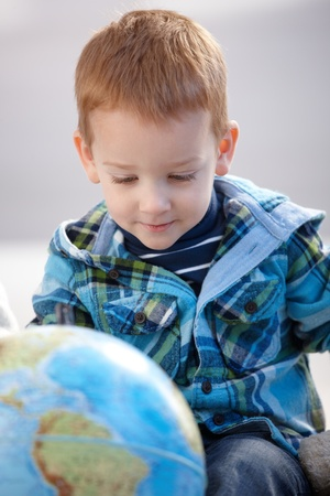 Sweet little boy studying globe at home, smiling. photo