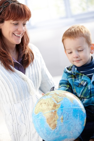 Mother and son playing with globe at home, smiling. photo