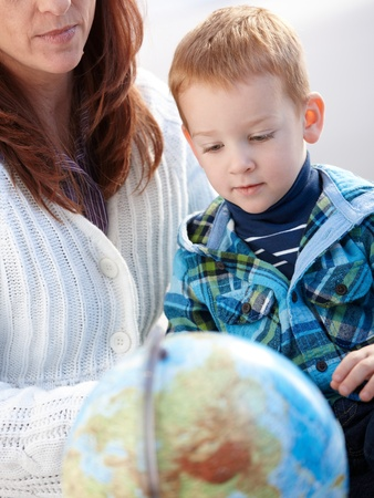 Mother with ginger-haired little boy studying globe at home. photo