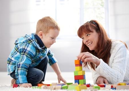 gingerish: Madre feliz y canci�n juntos jugando en casa en piso. Foto de archivo