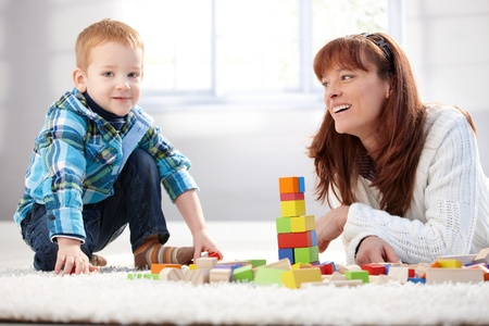 Mother and son building tower together at home, smiling. Stock Photo - 8747105