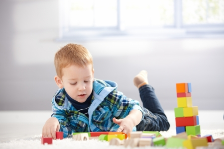 Cute 3 year old boy laying on floor, playing with cubes. photo