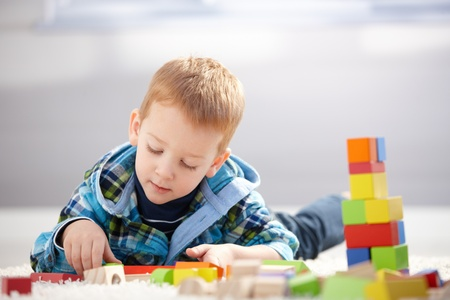 concentrating: Lovely toddler boy playing with building cubes at home, laying on floor.