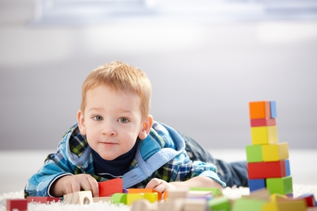 prone: Adorable little boy playing with building cubes at home, laying on floor.