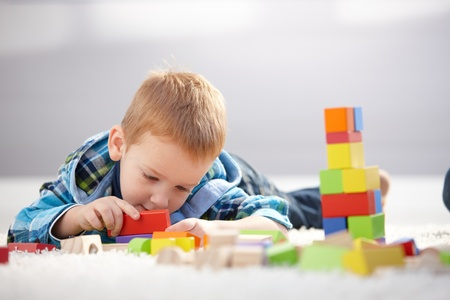 3 year old: Cute 3 year old laying on floor, lost in playing with building cubes.